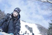 ゲレンデに座るスノーボーダー女性