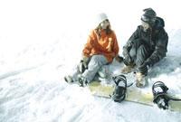 雪の上に座るスノーボーダー女性2人