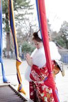 神社でお参りをする振袖姿の女性