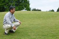 草原でしゃがむシニア男性
