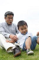 芝生に座るシニア男性と男の子