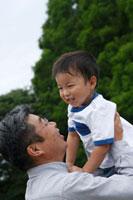 男の子を抱き上げるシニア男性