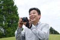 カメラをかまえるシニア男性