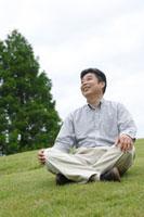 芝生に座るシニア男性