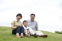芝生に座るシニア夫婦と孫