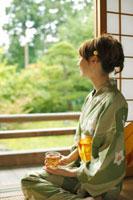 和室で麦茶を飲む浴衣の女性