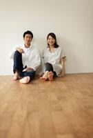 フローリングの床に座るカップル
