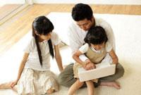 ノートパソコンを見る父親と姉妹