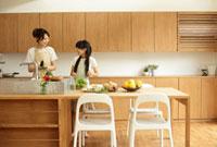 キッチンに立つ母親と女の子