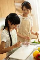 料理をする母親と女の子