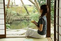 庭を眺めながら冷茶を飲む女性