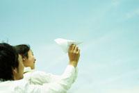 紙飛行機を飛ばす女の子と父親