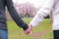 桜の木の前で手を繋ぐ