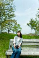 ベンチに座りながら写真を撮る女性