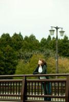 橋に寄りかかり遠くを眺める女性