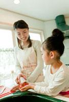 キッチンに立つ女の子と母親