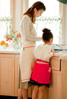 キッチンでお手伝いをする女の子と母親