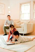 ノートパソコンを見る子供たちとソファでくつろぐ父親