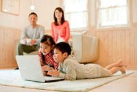 ノートパソコンを見る子供たちとソファでくつろぐ両親