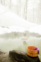 冬の露天風呂と桶と手ぬぐい