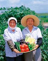 野菜を持った農家の老夫婦