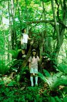 木のそばに立つ女の子2人