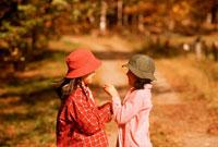 秋の道の女の子2人