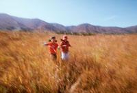 秋の草原を走る女の子2人 20014001117| 写真素材・ストックフォト・画像・イラスト素材|アマナイメージズ