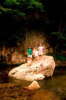 川の岩の上の子供達5人