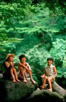河原の石の上に座る子供3人 20014002733| 写真素材・ストックフォト・画像・イラスト素材|アマナイメージズ