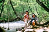 河原の木の枝に座る女の子2人