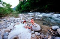河原の石の上に座る女の子2人