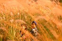 秋の草原の中の子供2人 20014002749| 写真素材・ストックフォト・画像・イラスト素材|アマナイメージズ
