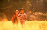 秋の草原を歩く子供2人 20014002751| 写真素材・ストックフォト・画像・イラスト素材|アマナイメージズ