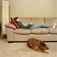 Teenage girl on sofa near dog on floor