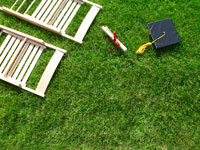Diploma and mortarboard on lawn