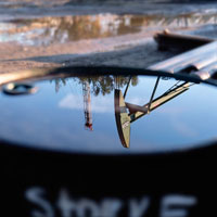 Reflection of oil rig on oil drum lid