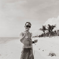 Man on beach with cigar and drink
