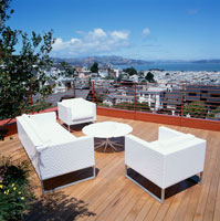 White couch and armchairs on roof deck