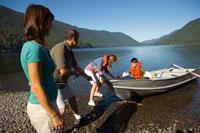 Family pulling rowboat onto beach