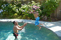 father catching son in swimming pool