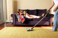 Man vacuuming while Hispanic girlfriend