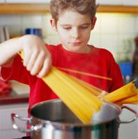 a boy  boils spaghetti in a kitchen