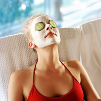 a woman having a face mask with cucumber