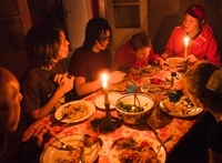 Family with teenage boys eating candlelit dinner
