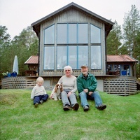 Senior couple with grandson sitting on grass