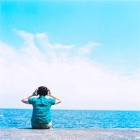 海で音楽を聴く女性の後姿 20021000331| 写真素材・ストックフォト・画像・イラスト素材|アマナイメージズ