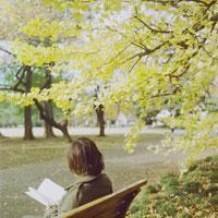 ベンチで読書する女性