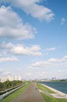 河川敷の道を走る自転車と空 20021000954| 写真素材・ストックフォト・画像・イラスト素材|アマナイメージズ