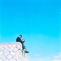 空を見上げて座るカップルと青空